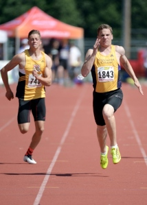 Vancouver College sprinter Anastas Eliopoulos (right) surges for the finish line to win the junior boys 100 metre dash. He won triple gold by also winning the 200 metre dash and the 100 metre hurdles at the B.C. high school championships at McLeod Athletic Park on June 5, 2015. Photo Jennifer Gauthier